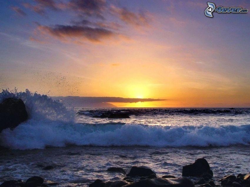 wave, sunset behind the sea, rocky beach