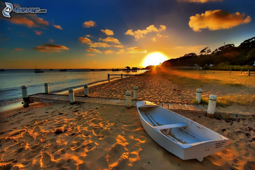 wooden boat, sandy beach, wooden pier, sunset behind the sea