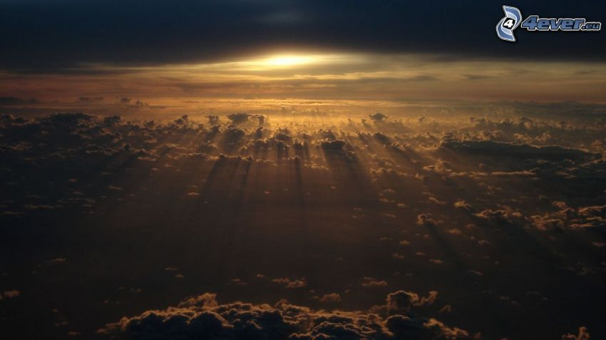 sunbeams behind clouds, over the clouds