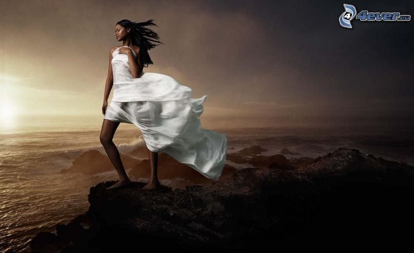 girl on the reef, black woman, white dress, sunset behind the sea, the view of the sea