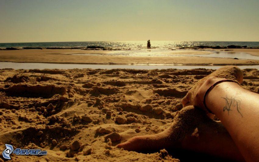couple in the sea, sandy beach, legs, sea, tattoo on foot