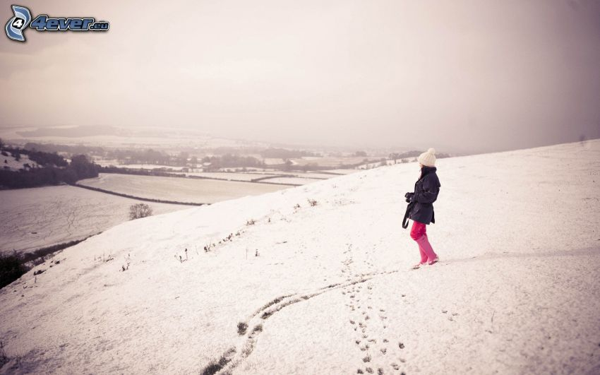 girl on the snow, view of the landscape, tracks in the snow