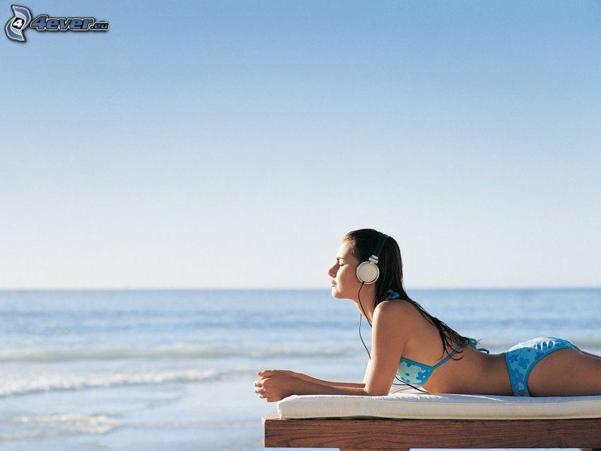girl with headphones, sunbathing, open sea