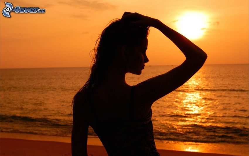 silhouette of woman at sunset, sunset over ocean, orange sky