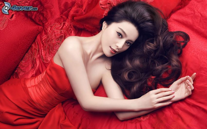 woman in bed, brunette, red dress
