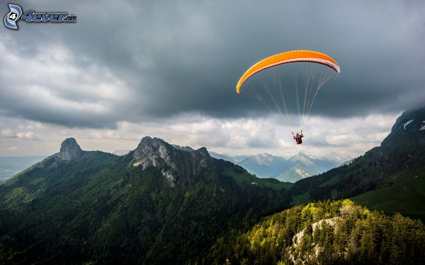 paragliding, rocky mountains, dark clouds