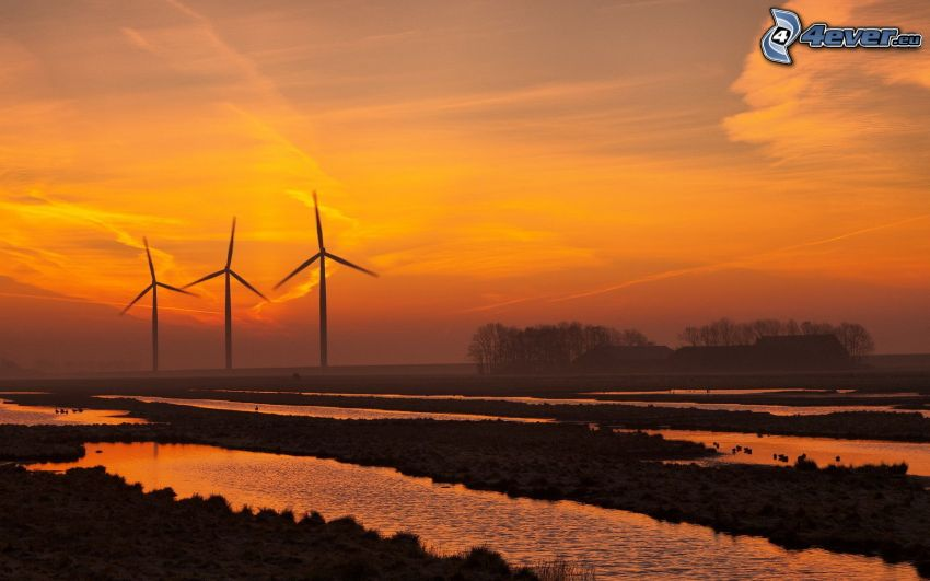 wind turbines at sunset, orange sky, puddles