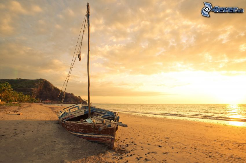 Old boat on the beach, sunset