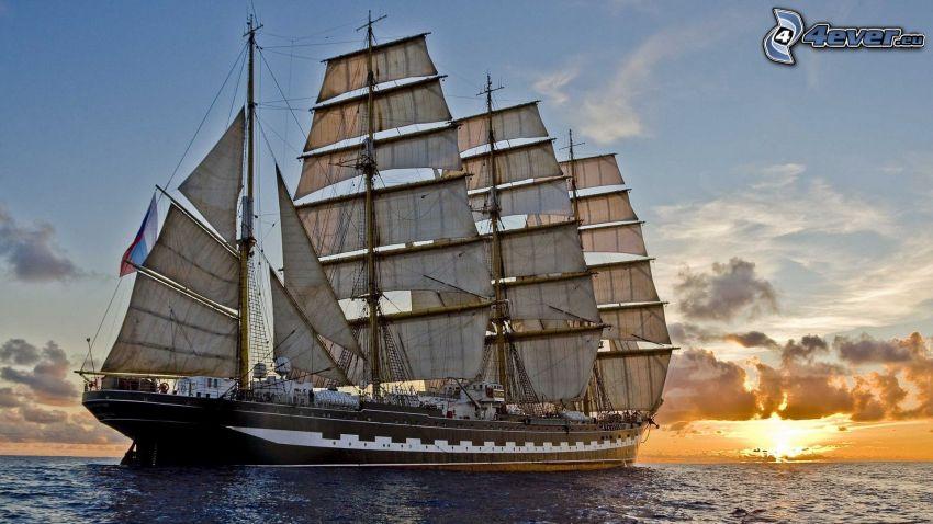 sailing boat, sunset behind the sea