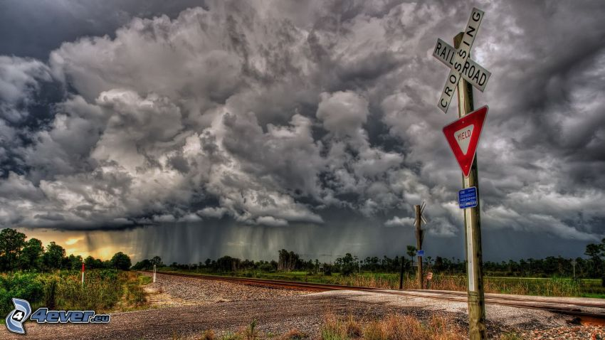 rail crossing, road sign, dark clouds